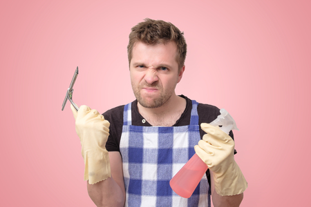 European young husband is tired of washing glass on pink background.