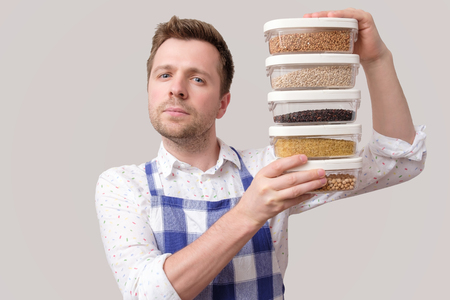 Young smiling man in apron hold several boxes with grains.