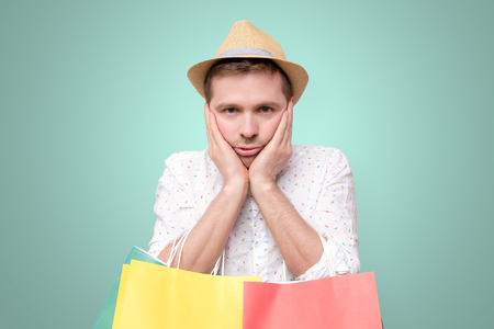 Bored european man leaning on palm. holding packets after shopping