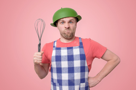 crazy man in an apron with a colander on his head Banco de Imagens
