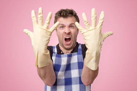 Mature european man with rubber gloves is tired and annoyed with house hold chores Stock Photo
