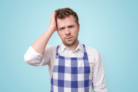 Man in apron having puzzled look going to make serious decision what to cook for dinner.