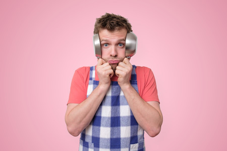 Man in apron covering his ears with pans. Imagens