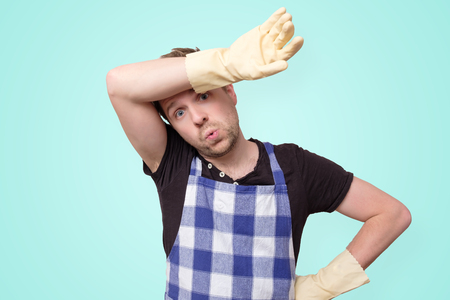 Man wearing rubber gloves for hands protection wiping sweat