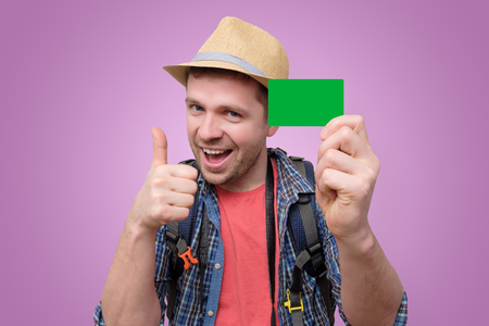 Young handsome tourist man holds green credit card.