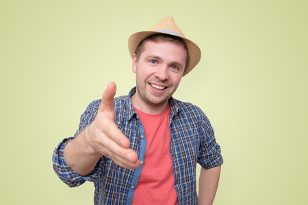 Young man in summer hat shake hand with you