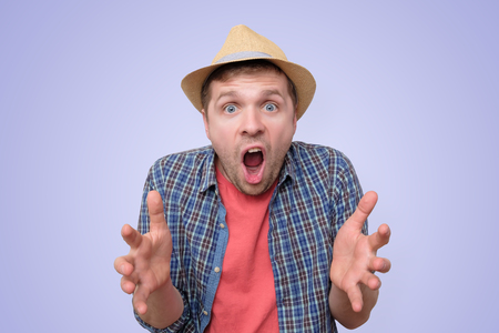 man in summer hat with shocked expression, screaming