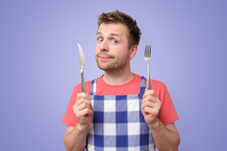 Man in apron holding cutlery fork and knife