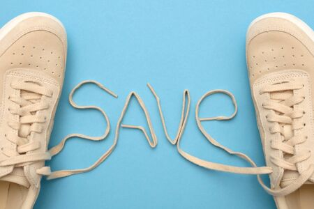 New women sneakers with laces in save text. Stock Photo