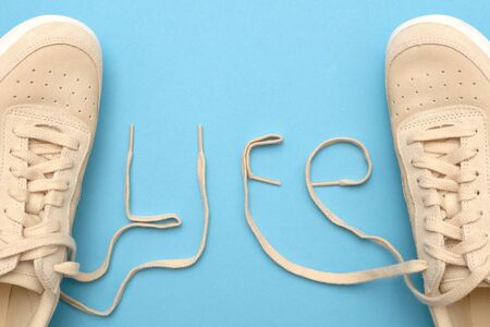 New women sneakers with laces in life text.