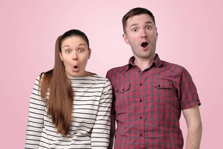 Excited shocked man and woman look with widely opened mouth