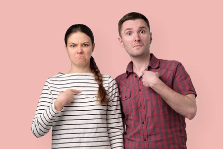Young couple pointing fingers, having doubtful emotion