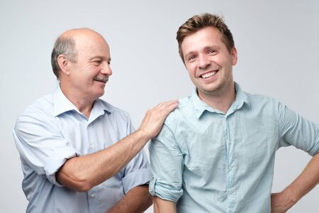 Cheerful father and son looking at each other smiling Imagens