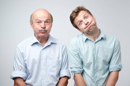 Two men grimacing, inflating cheeks, holding breath