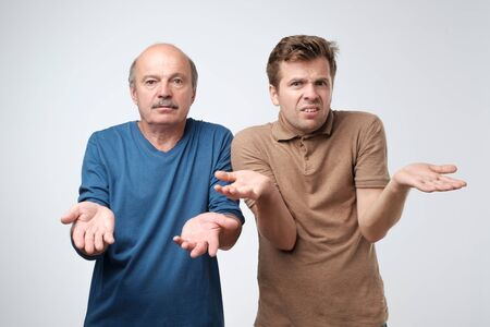 father and son raise hands as shows being confused