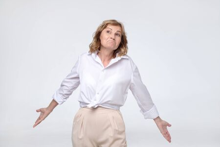 Pretty mature woman retired boss looking confused shrugs her shoulders. Stock Photo