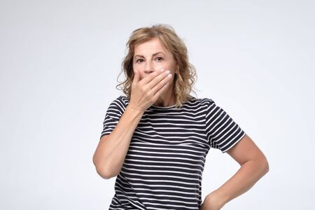 Surprised mature woman covering mouth with hand and staring at camera