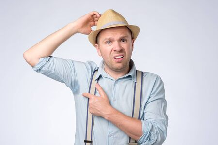 Doof Mann mit Sommerhut ist besorgt und schockiert wegen Schwitzflecks. Standard-Bild