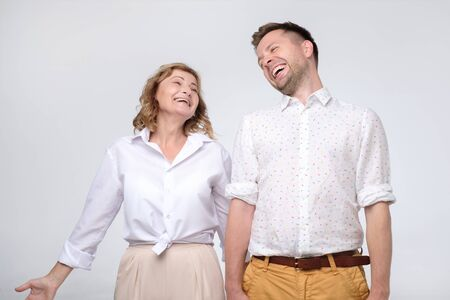 Mature woman and man giggling on funny joke.