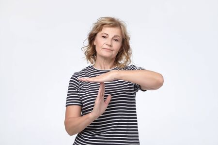 Serious worried mature woman showing time out sign
