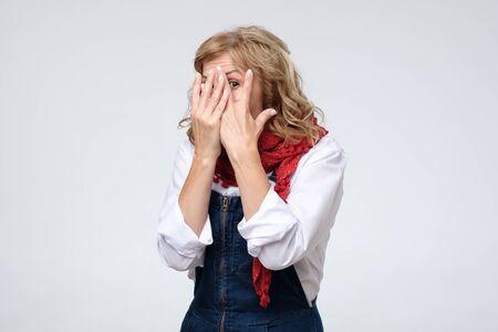 Reife Frau versteckt ihr Gesicht, Studiofoto