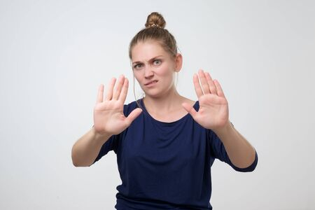 Unhappy caucasian woman with hair bun showing stop or enough gesture with hand, frowning and expressing dislike. stay away from me or do not come closer Banco de Imagens