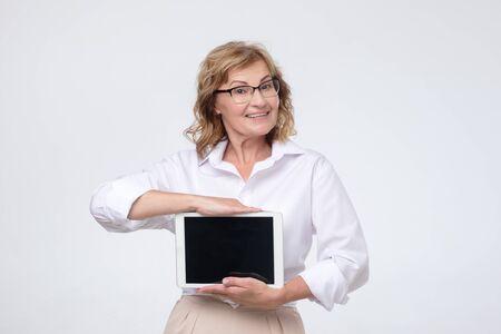 Mature caucasian woman shows a screen digital tablet.