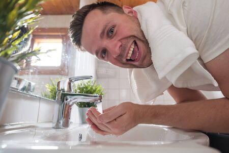 Caucasian man washing face in a wash basin in white washroom
