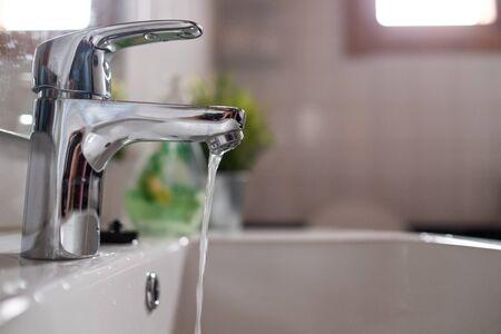 Lavabo de grifo abierto con baja presión de agua Foto de archivo