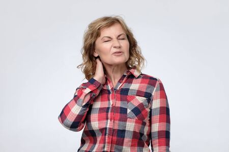Mature woman is having pain in her neck. 写真素材