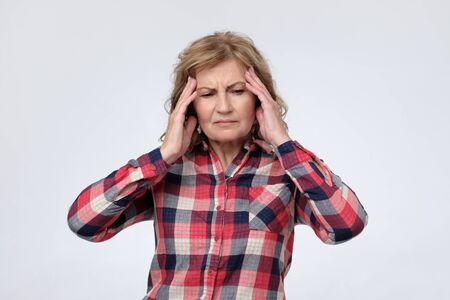 Mature caucasian woman suffering from headache and pain. 写真素材
