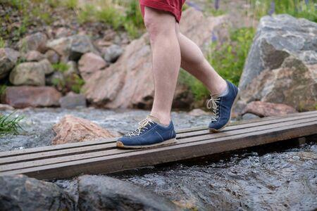 Man walking on a wooden bridge crossing water stream