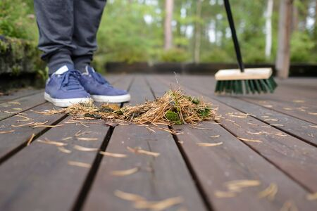 sweeping a wooden flooring with a mop from pine needles