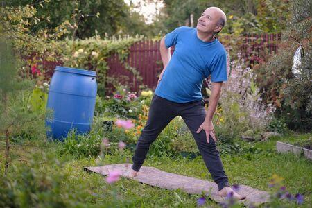 Senior hsipanic man i working out on river bank in garden, standing in Utthita Trikonasana Stockfoto