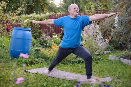 Senior hsipanic man is working out in garden, standing in Virabhadrasana 2 or warrior pose Stockfoto