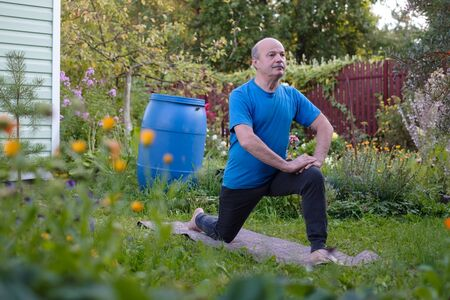 Man is working out in garden, standing in Virabhadrasana 1 or warrior pose