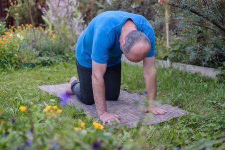 Senior man working out in yoga, pilates bend in Cat yoga Pose, Marjaryasana Stockfoto