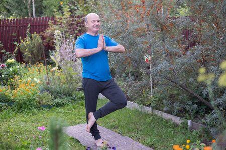 Senior hispanic man standing in tree yoga pose in garden Stok Fotoğraf