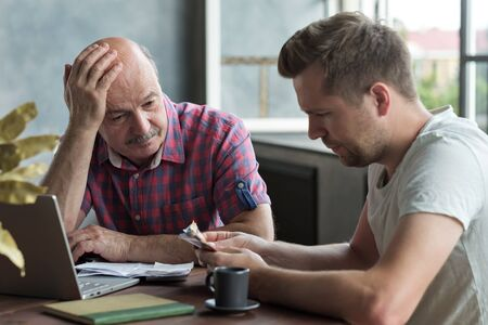 Sad and stressed elderly father and his adult son counting money. Have troubles with taxes and debts
