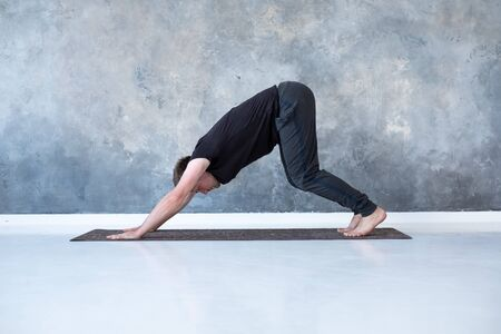 Young man working out, standing in yoga downward facing dog pose Stock fotó