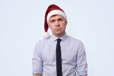 man wearing red christmas cap is upset because he is tired of working in office. Stock Photo