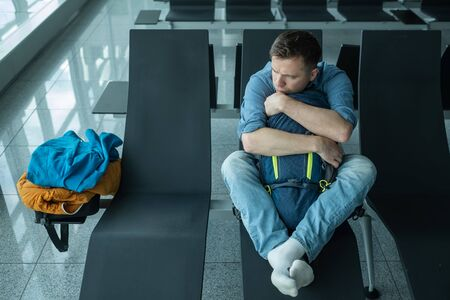 Young man at the airport waiting for his plane looking at the window