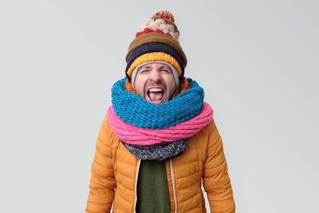 Young man in winter hat and scarf shouting Banco de Imagens