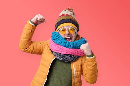 Young male in orange summer glasses and winter scarf clenches fists in joy, like a winner