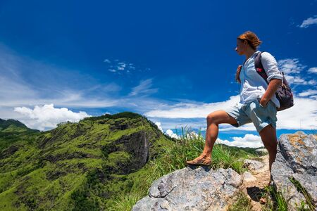 Woman enjoying beautiful view of cloudy sky and hills from the top of Small Adams peak near Ella