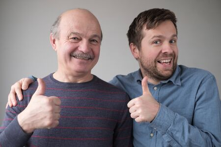 Two caucasian mature men father and son look at camera show thumbs up Stockfoto