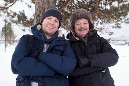 Attractive caucasian senior and young men standing outdoors in snow winter day