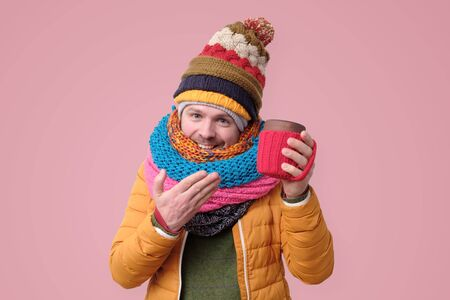 Handsome hipster man in hat, scarf holds cup with hot coffee or tea. Studio shot on pink background. Stockfoto