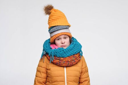 Young woman in several hats and scarfs does not like winter time looking at camera with sad expression. I am cold concept. Studio shot