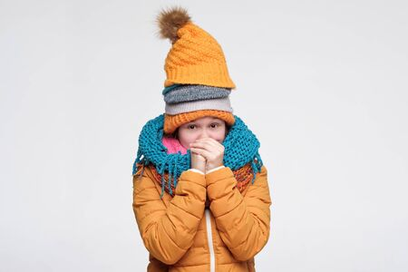 Funny young caucasian woman shivering from cold wearing several warm winter hats and scarfs. Studio shot